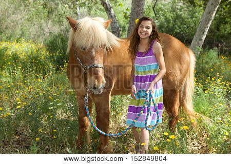 A cute little girl and her Icelandic Pony Friend smiling in a flower field.