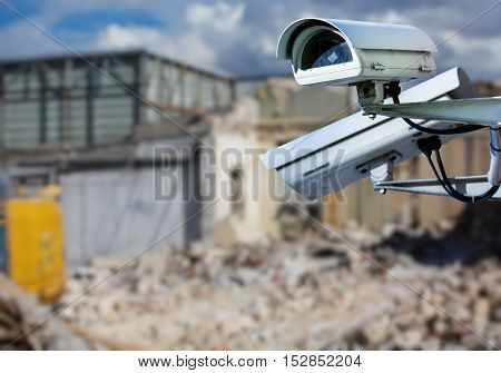 security CCTV camera or surveillance system with construction site on blurry background poster