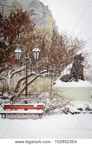 Winter city park in snow. Bench and a monument trees in snow