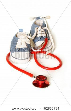 Isolated denim baby shoes and a doctors stethoscope representing childcare prediatrics.