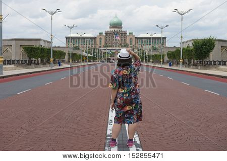 woman stand his back at government house mosque middle of road no car and traffic
