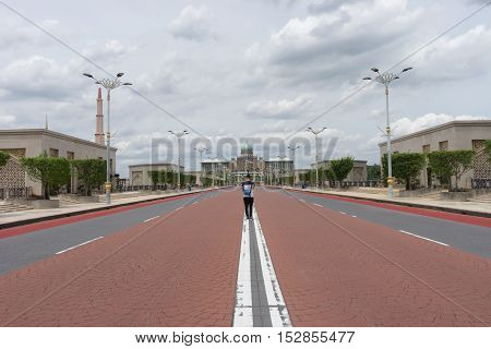 man stand his back at government house mosque middle of road no car and traffic / man road mosque