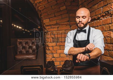 artisan shoe shiner rolls up his sleeves in front of a pair of shoes