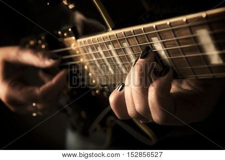 Close up view on a musican hand playing guitar