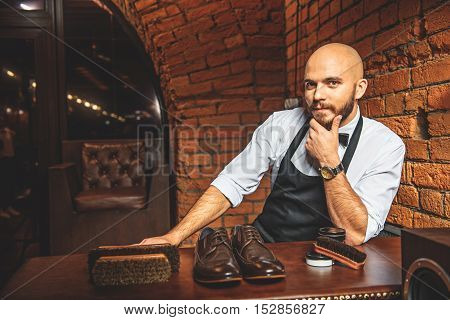 bald bearded man sitting near his workplace with equipment and looking into a camera