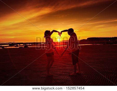 Man and woman at sunset, composite symbol of the hands in the form of heart.