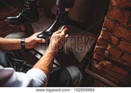 guy shining shoes on ankles of the customer, close up