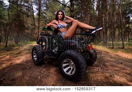 Elegant woman sitting on quadrocycle ATV in forest