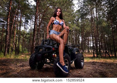 Beautiful Girl Standing Between Two Four-wheelers Atv. Smiling And Looking Towards The Camera. Tilt