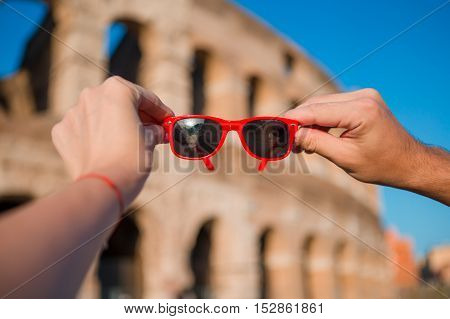 Close up sunglasses in front of colosseum in rome, italy