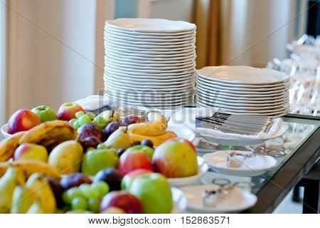 banquet table covered with stacks of white plates and fruit