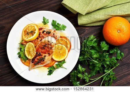 Grilled chicken breast with orange sauce on wooden background top view