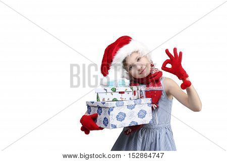 Christmas, X-mas, holidays, children, people concept - portrait of little girl in Santa helper hat holding colored present boxes over light background