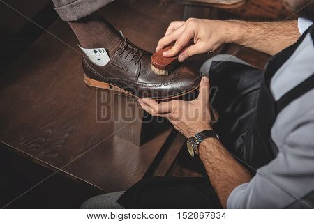 shoeshine man cleaning leather brogues with a horse brush poster