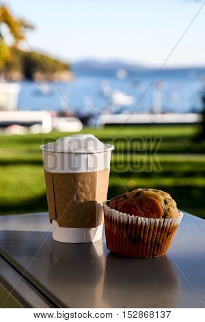 Paper cup with coffee and muffin