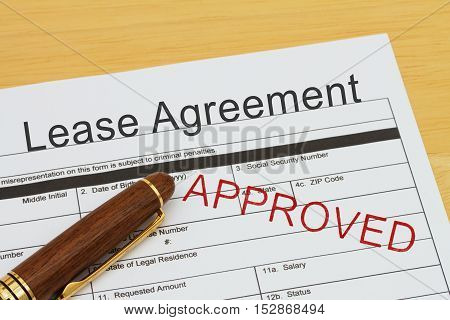 Applying for a Lease Agreement Approved Lease Agreement application form with a pen on a desk with an approved stamp