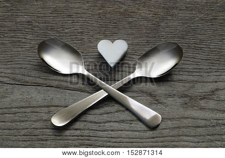 White sugar heart with two crossed spoons on wooden background