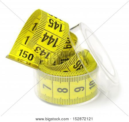 Measuring tape in a box on white background