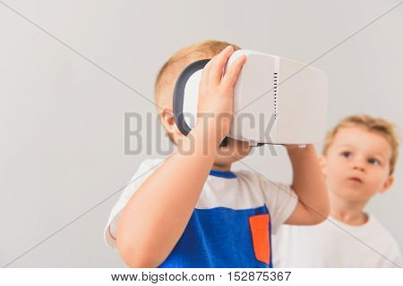 This is my turn to play. Cropped photo of little boy watching though virtual reality device with his friend on background isolated on grey wall