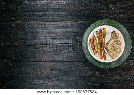 Porkchop and baby carrots baked and served on the plate