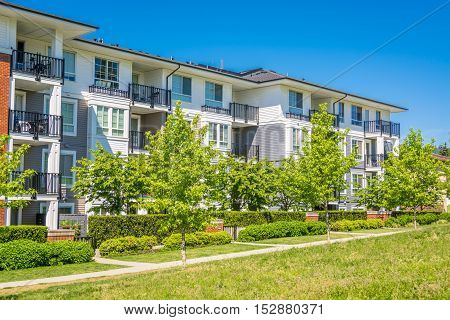 Brand new condo building on sunny day in British Columbia Canada. Luxury apartment building with green lawn in front