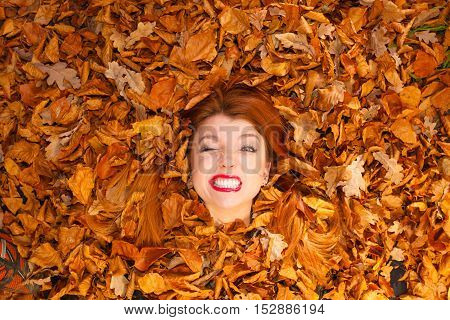 Happiness art beauty makeup concept. Young lady covered by leaves. Red hair girl sticking her head out of foliage pile smiling.