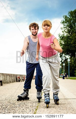 Active young people friends in training suit rollerskating outdoor. Happy woman and man riding enjoying sport.