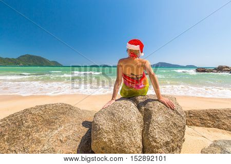 Beautiful, fashionable woman with red Santa Claus hat relaxing and catching tan on rocks in tropical Laem Ka Beach for the Christmas holidays. Phuket, Thailand.
