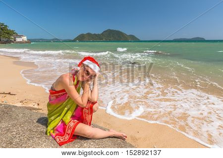 Christmas in the tropics. Beautiful woman with red Santa Claus hat relaxing on rocks in tropical Laem Ka Beach for the Christmas holidays in Phuket, Thailand. Christmas vacation concept.
