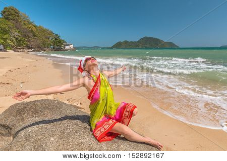 Beautiful woman with red Santa Claus hat enjoy and catching tan on rocks in tropical Laem Ka Beach for the Christmas holidays. Phuket, Thailand.