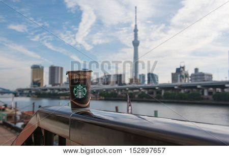 TOKYO  , JAPAN - OCTOBER 13 ,2016 : cup coffee Starbucks in Tokyo , view Skytree and Sumida River background.