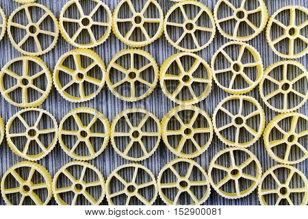 Wagon wheel pasta on a grey background filling the frame