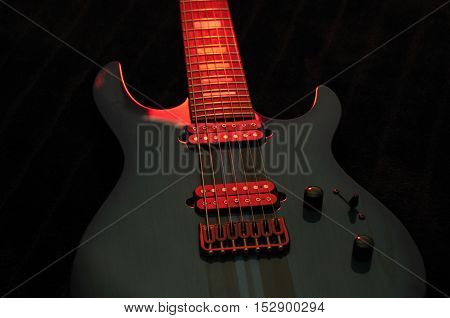 Closeup of blue electric guitar with red light