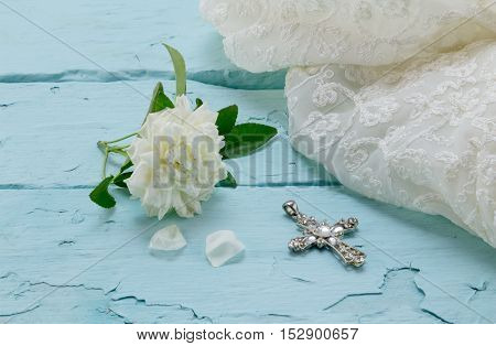 Cream rose cream lace dress and crystal cross on rough painted wood background