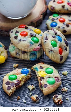 Shortbread cookies with multi-colored candy and chocolate chips on wooden table vertical