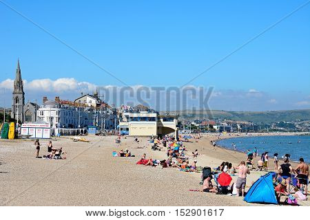 WEYMOUTH, UNITED KINGDOM - JULY 18, 2016 - View along the beach and promenade with holidaymakers enjoying the setting Weymouth Dorset England UK Western Europe, July 18, 2016.