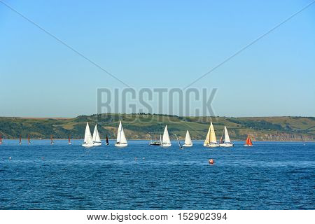 WEYMOUTH, UNITED KINGDOM - JULY 18, 2016 - Yachts and dinghy sailing on the bay Weymouth Dorset England UK Western Europe, July 18, 2016.
