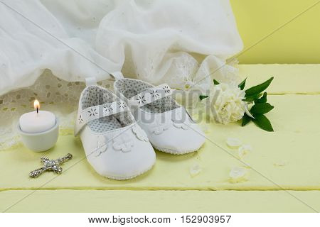 Christening background of vintage lace dress on yellow wood table with baby booties candle rose and cross pendant