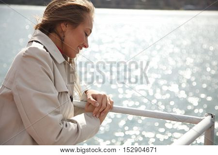 Young beautiful woman standing near water line and looking down.Copyspace