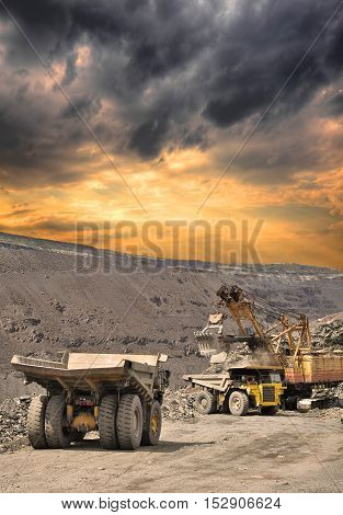 Heavy dump trucks being loaded with iron ore on the opencast on stormy sunset