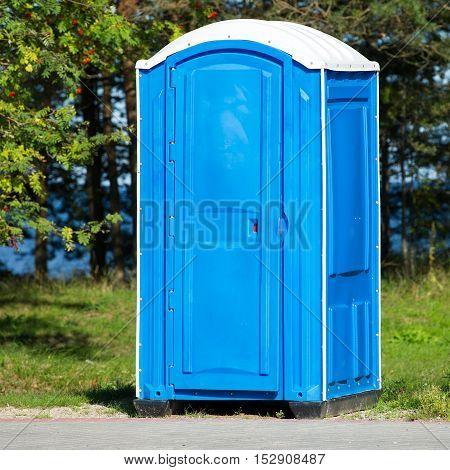A blue portable bio-toilet cabin in the park