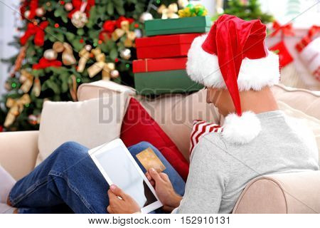 Young man shopping online with credit card at home for Christmas