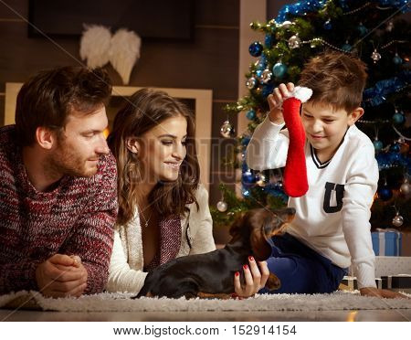 Attractive young family playing on floor with Dackel puppy received for christmas.