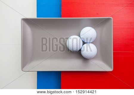 Gray ceramic dish with golf equipments on over whiteblue and red wooden table rectangle dish