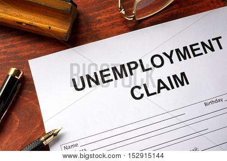 Unemployment claim form on an office table. poster