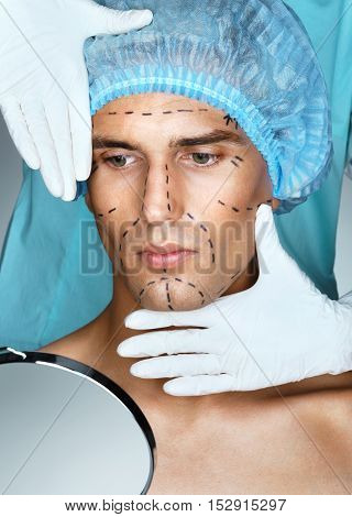 Young man patient with perforation lines on his face before plastic surgery operation. Nurse touching man face. Beauty face concept