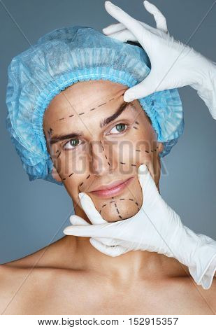 Nurse touching man face. Close up of male with perforation lines on skin for cosmetic medical procedures. Guideline marks on eyes nose cheek and jaw
