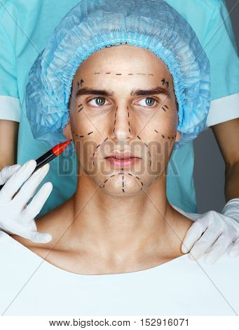 Doctor draws guideline marks on face of patient. Face of young man before plastic surgery. Beauty Face