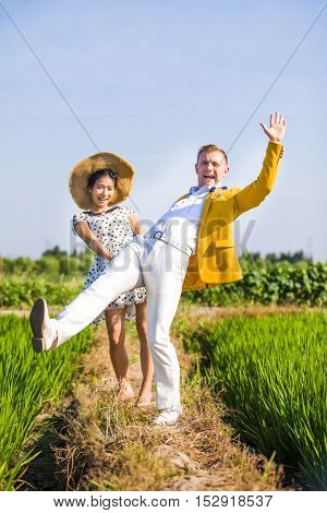 Multi racial couple falling over in a field, they look like they are having a lot of fun. He is stylishly dressed in a yellow jacket and she is wearing a summer dress and straw hat