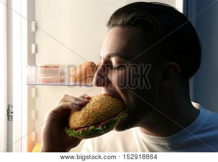 Handsome man eating sandwich in kitchen. Unhealthy food concept
